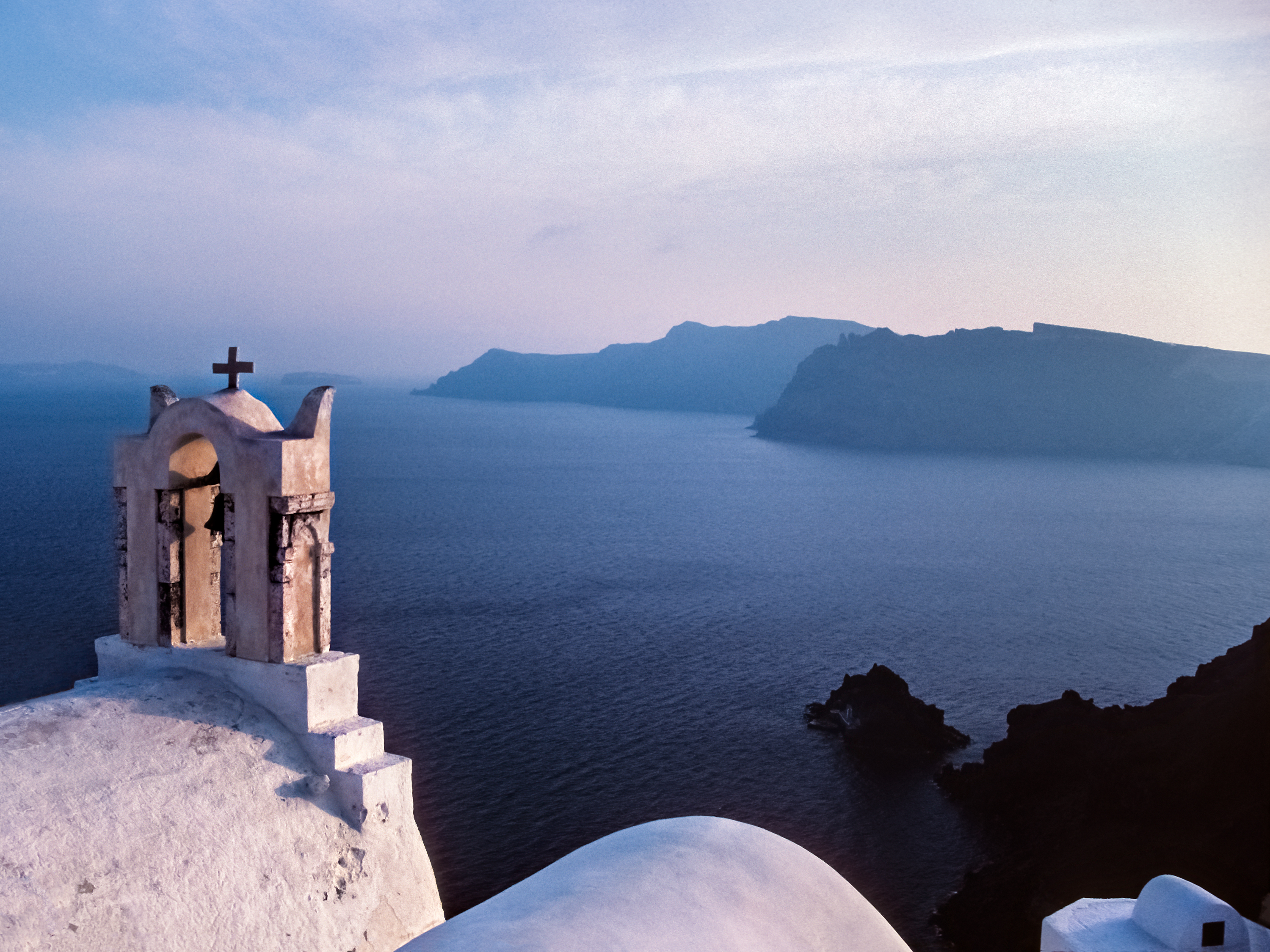 The coast of Thirasia and volcano as seen from a church in Oia on the island of Santorini, Greece by Peter Adams.